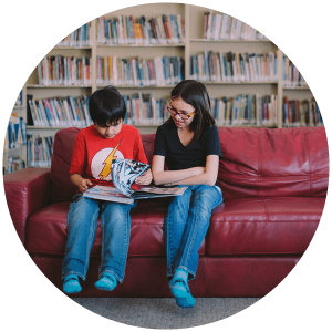 Chase and Nadine read a book on a couch in a library.
