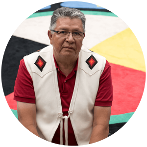Randy sits on a medicine wheel carpet in a Calgary agency