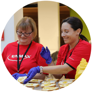Enmax employees smile while volunteering to make sandwiches for Calgarians in need.