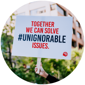 A hand holds up a sign that reads ``Together we can solve #unignorable issues.``