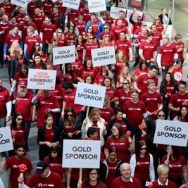 A team from Pembina Pipeline Corporation marches in United Way's kickoff holding gold sponsor signs.