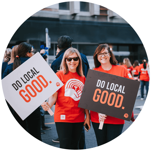 "Two United Way employees hold up signs at campaign kickoff that read ""do local good."""