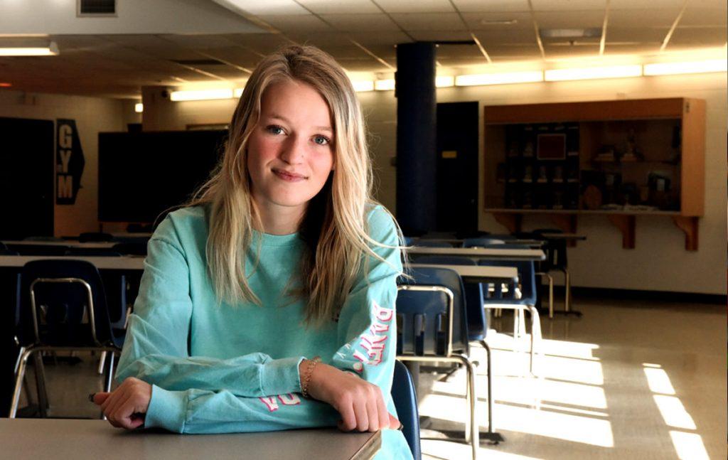 A photo of Bryanna sitting in a school classroom.