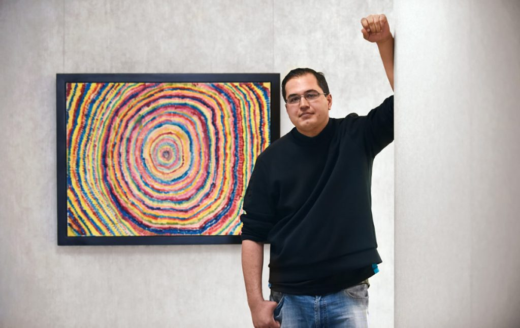 A photo of Travis with some of his art.