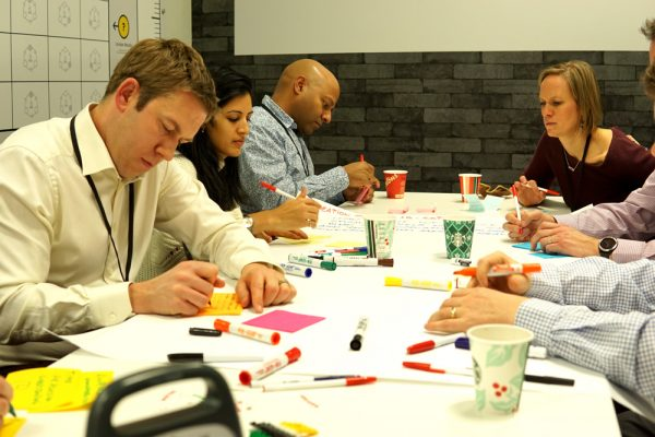 A photo of people working around a meeting table.