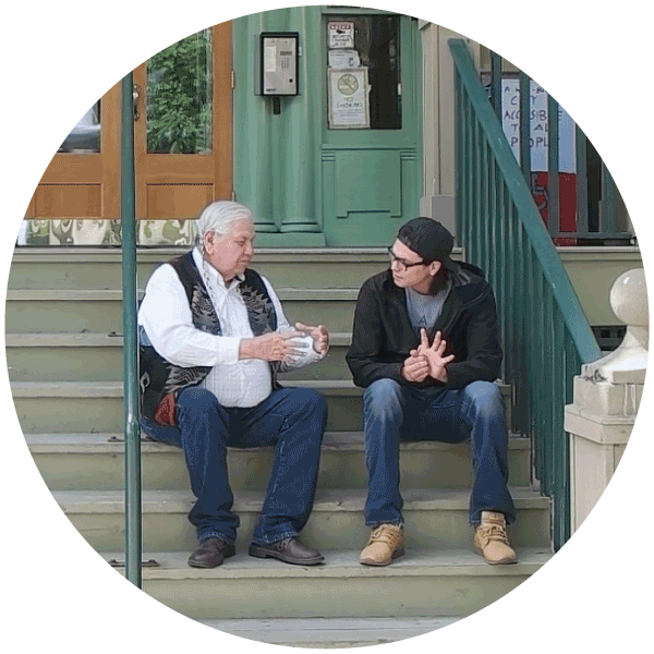 Reg and Johnny sit on the steps in front of the Diamond Willow Youth Lodge