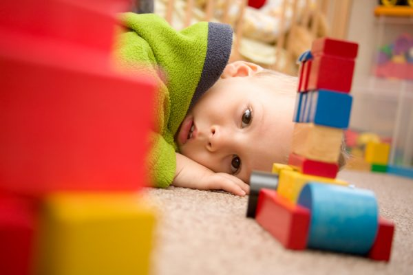 A toddler looks at blocks on the floor