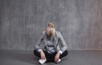 A woman lowers her head in an empty room.