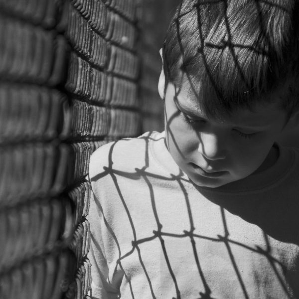 boy looking serious leaning against a fence