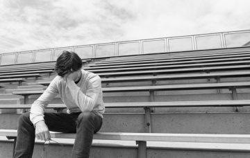 Depressed teen in bleachers