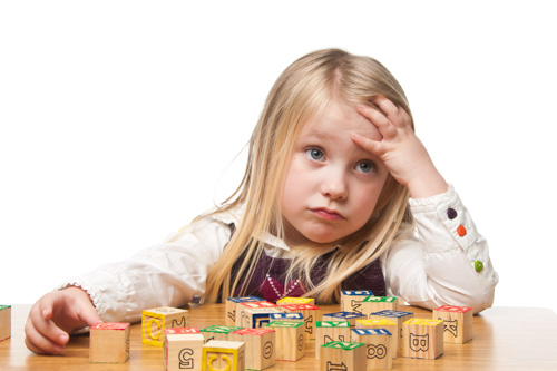 A child looks puzzled while playing with blocks