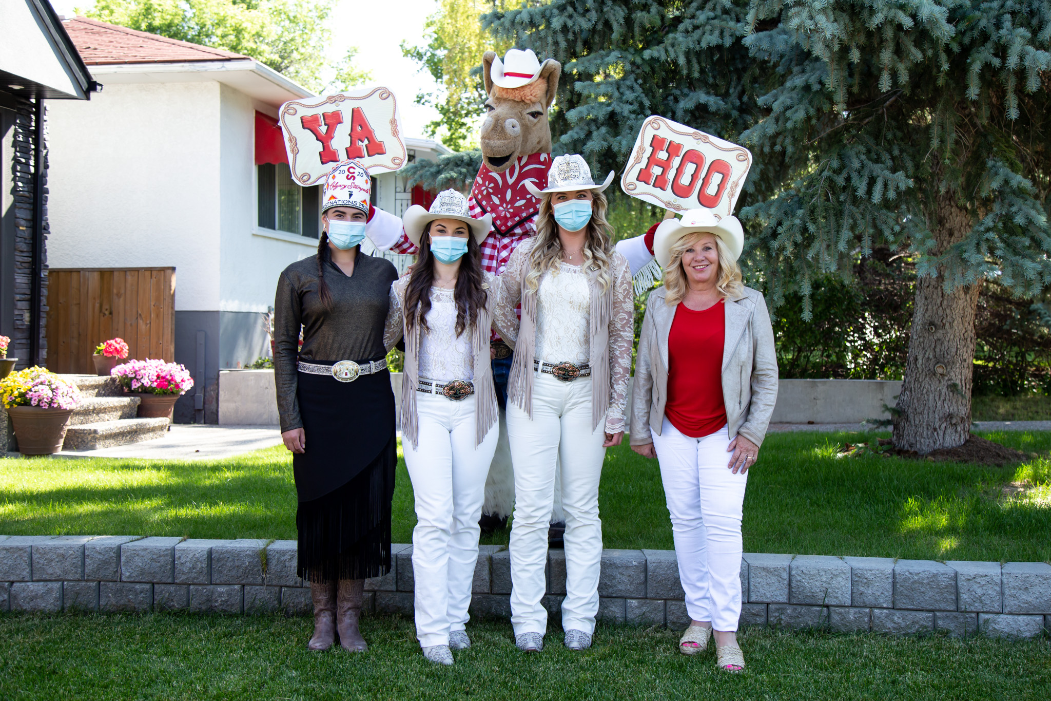 Group shot of the Stampede Princess' with Harry the Horse holding Ya Hoo signs