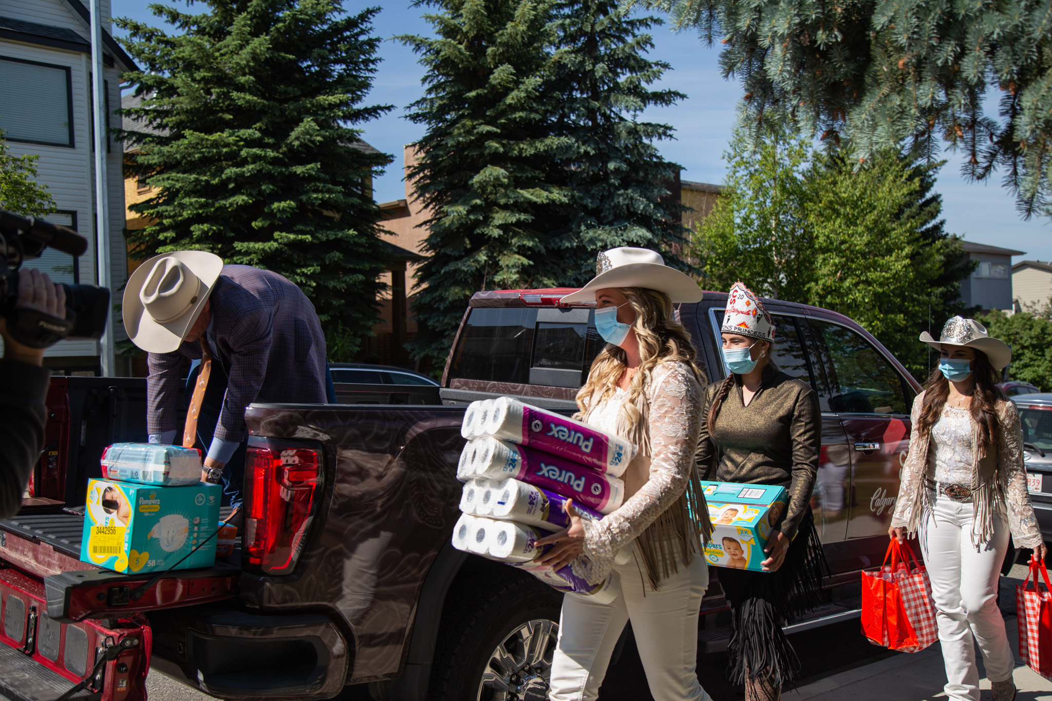 Group shot of the Stampede Princess' loding donation items and toilet paper into the back of a truck on a sunny day