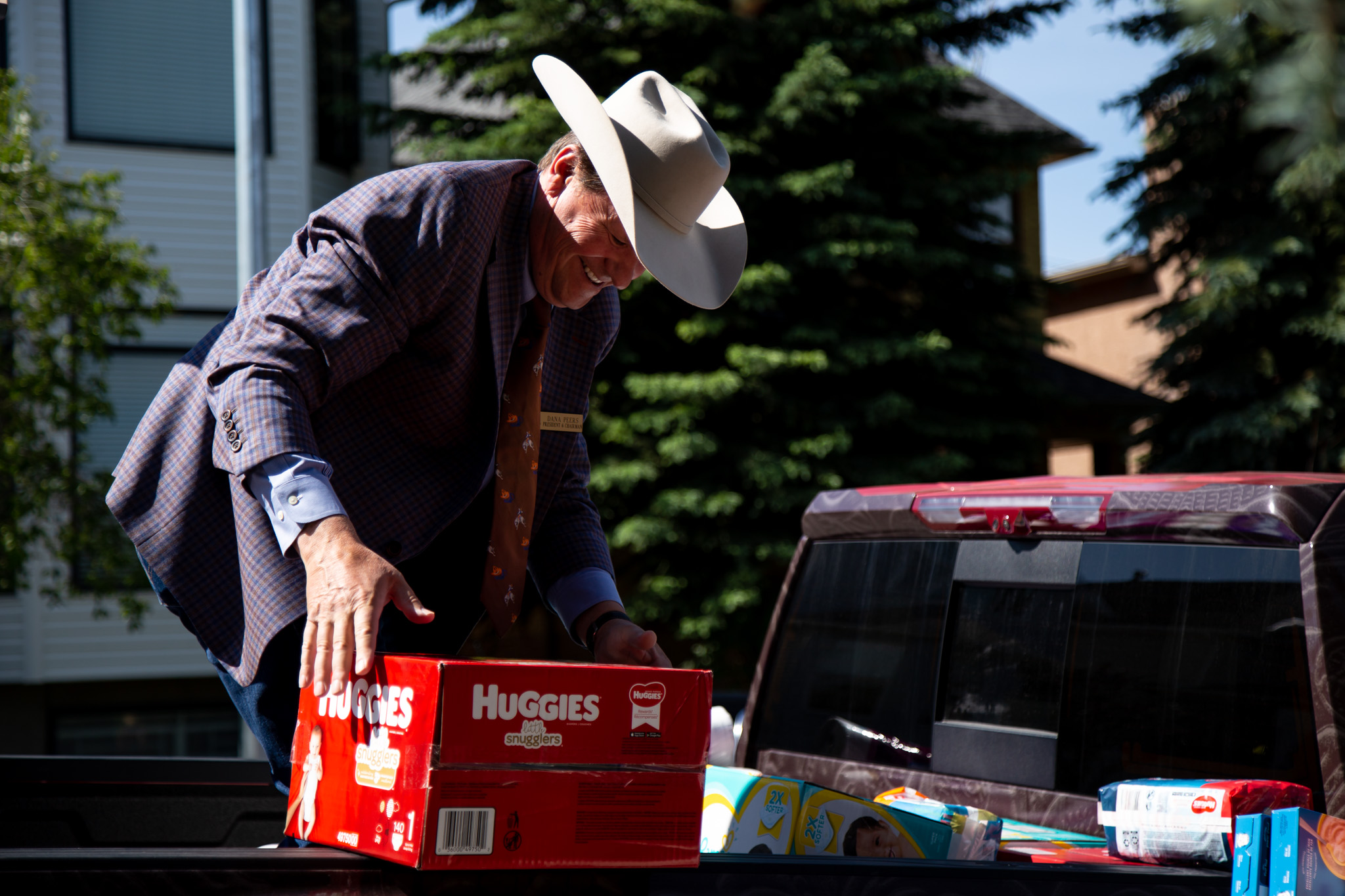 Stampede official smiling and loading a box of diapers into the back of the truck