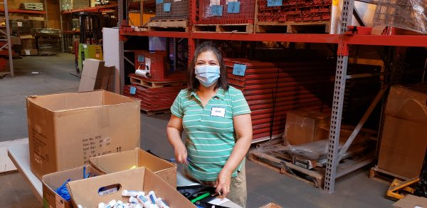 Women working in a warehouse wearing a face mask