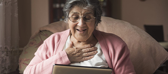 Women with her hand over her heart, smiling while reading tablet