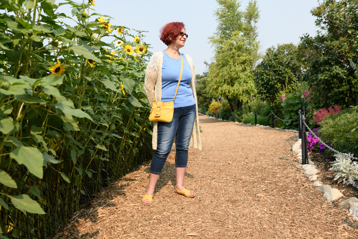 Laura stands besides sunflowers